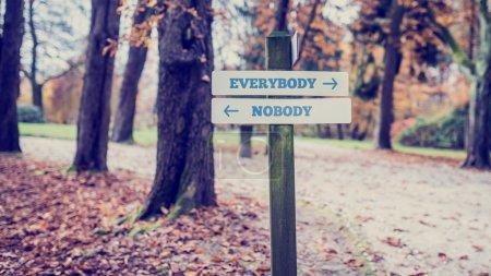 Photo pour Panneau dans un parc ou une zone boisée avec des flèches pointant deux directions opposées vers Tout le monde et Personne . - image libre de droit