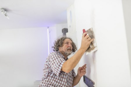 Middle-aged male builder or homeowner plastering a...