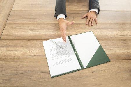 Photo pour Homme d'affaires attendant de serrer la main au-dessus d'un contrat disposé pour la signature sur le bureau en face de lui dans une image conceptuelle, fermez l'angle élevé de la paperasse et la main. - image libre de droit