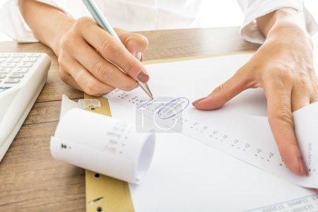 Photo pour Gros plan Femme d'affaires Calcul des dépenses sur les reçus imprimés à son bureau avec calculatrice sur son côté . - image libre de droit