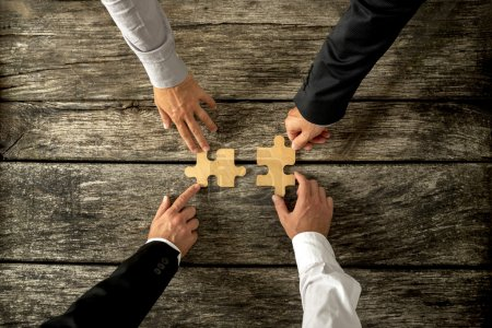 Photo for Four successful business men joining two puzzle pieces each being held by two partners, rustic wooden background. Conceptual of merger or creative cooperation of two business companies. - Royalty Free Image