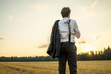 Photo pour Jeune homme d'affaires prospère se tenant dans le champ de blé regardant vers l'avenir alors qu'il décide de nouvelles étapes et orientations à prendre dans sa carrière . - image libre de droit