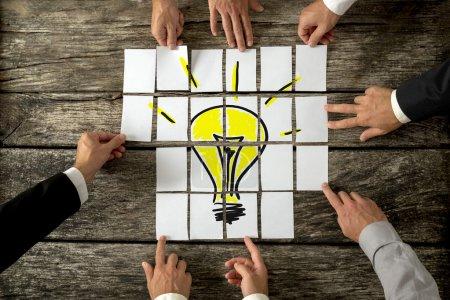 Photo pour Vue d'angle élevé des mains d'hommes d'affaires touchant les livres blancs disposés sur une table en bois rustique formant une ampoule jaune. Conceptuel pour affaires brillantes idées et innovations. - image libre de droit