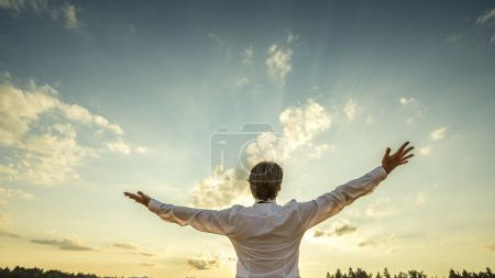 Photo for Successful man in elegant white shirt standing with his back to the camera with his arm spread widely towards beautiful majestic evening sky as he celebrates his success and prosperity. - Royalty Free Image