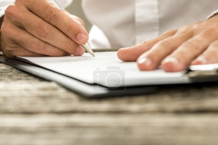 Low angle view of male hand signing contract or subscription for