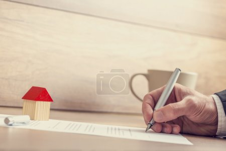 Closeup of male hand signing insurance papers, contract of house