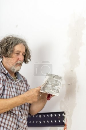 Builder repairing a crack in a wall
