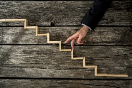Businessman or student walking his fingers up wooden steps