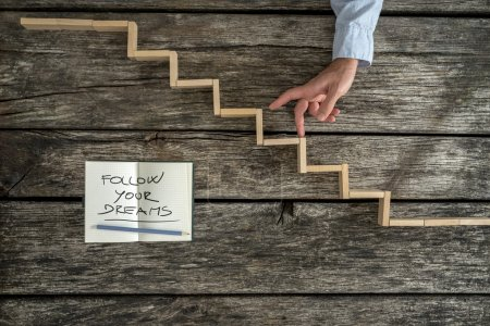 Male hand walking his fingers up wooden steps with a Follow your