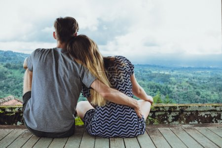 Back view of a young man and woman enjoying amazing view while s