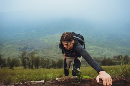 Photo for Hiker man climbing a steep wall in mountain - Royalty Free Image