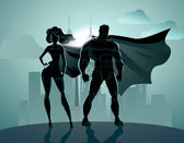 Superhero Couple: Male and female superheroes posing in front of a light City background