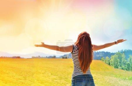 Photo pour Jeune fille écartant les mains avec joie et inspiration face au soleil - image libre de droit