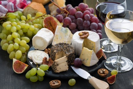 soft delicacy cheeses and snacks for wine on a dark background