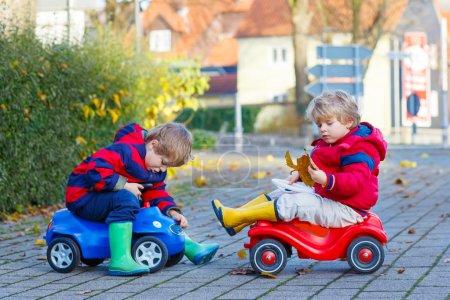 Foto de Dos niños pequeños con ropa de colores y botas de lluvia conduciendo coches de juguete y haciendo competencia, al aire libre. Ocio activo para amigos el día de otoño - Imagen libre de derechos