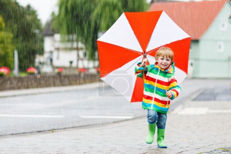 Photo for Little child having fun with red umbrella, wearing colorful raincoat and rain boots outdoors at rainy day - Royalty Free Image