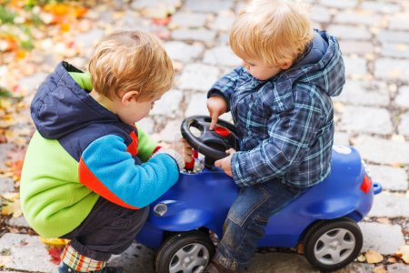Two little sibling children playing with toy car on autumn day.