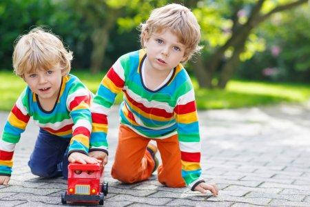 Photo pour Deux petits frères et sœurs, enfants garçons en vêtements colorés avec des rayures jouant avec un jouet d'autobus scolaire rouge dans le jardin d'été par une chaude journée ensoleillée. Apprendre à jouer et à communiquer ensemble . - image libre de droit