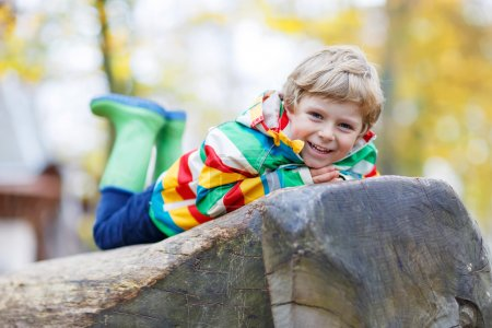 Photo for Adorable child in colorful rain jacket with stripes and gumboots having fun with playing on playground on warm, autumn day, outdoors - Royalty Free Image
