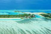 Tropical island on Bora Bora with water villas and coral reef.