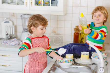 Two little lovely and funny kid boys washing dishes in domestic