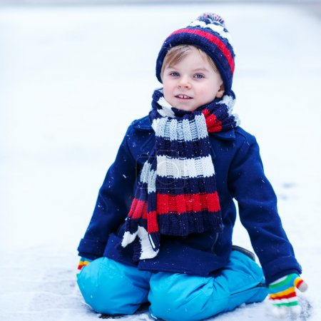Cute little funny boy in colorful winter clothes h...