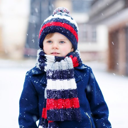Little boy playing with snow in winter, outdoors.