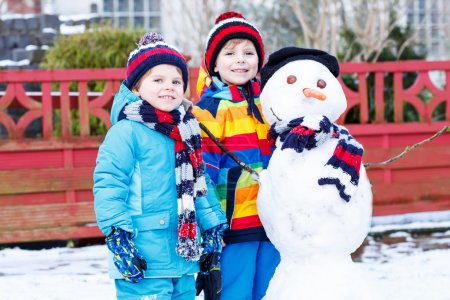 Two little siblings boys making a snowman, playing...