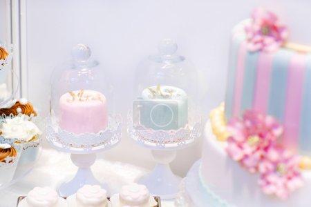 Photo pour Gâteaux de mariage en crème et rose avec des perles. Cupcakes pour mariée et marié avec lettres Mme et Mr. Cerise avec crème, massepain, détails du gâteau . - image libre de droit