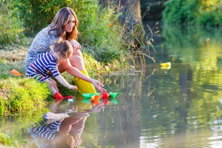 Adorable little girl and her mom playing with paper boats in a r