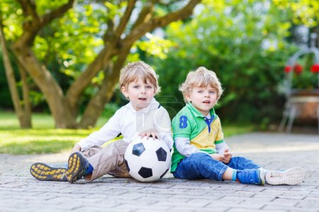 Two little sibling boys playing soccer and football