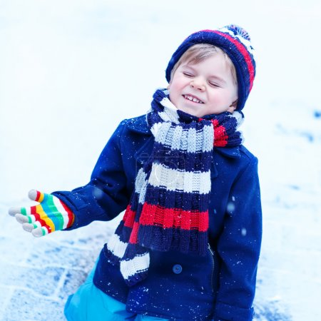 Funny and happy toddler boy in colorful winter clo...