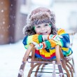 Cute little funny boy in colorful winter clothes s...