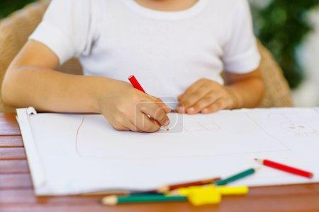 Hands of preschool kid boy making homework