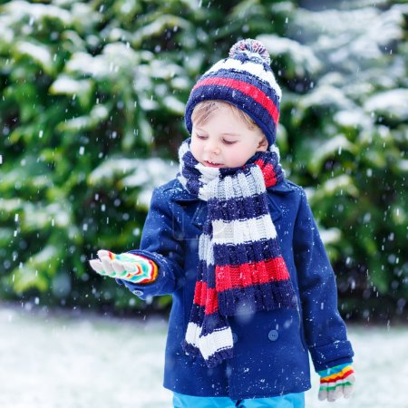 Cute little funny boy in colorful winter clothes c...