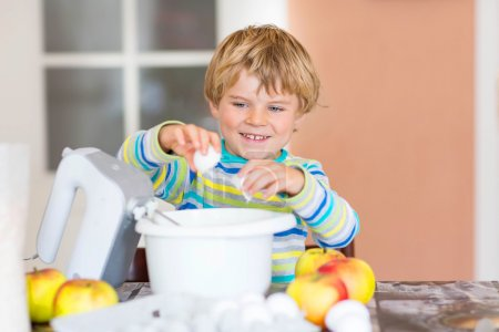 Photo for Cute funny blond kid boy of 4 years baking apple cake in domestic kitchen. Happy child having fun with working with mixer, flour, eggs and fruits. - Royalty Free Image