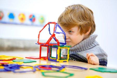 Little kid boy building geometric figures with plastic blocks