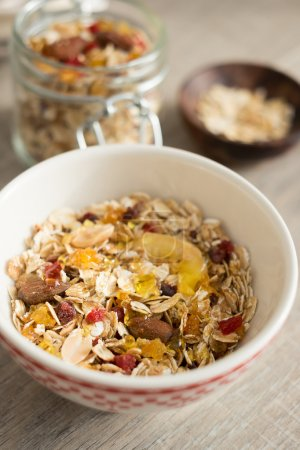 Homemade granola with oat flakes, honey, brown sugar, nuts and dried fruits in a jar, selective focus