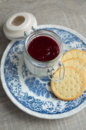 Vanilla panna cotta dessert with red berry sauce in a jar and cookies on a plate, selective focus