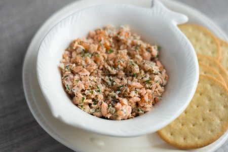 Roasted and smoked salmon and soft cheese spread with dill and butter served with cheese crackers, selective focus