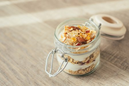 Homemade bircher muesli with toasted rolled oats, dried fruits, nuts, honey and fresh yogurt in a jar, traditional Switzerland breakfast meal, selective focus