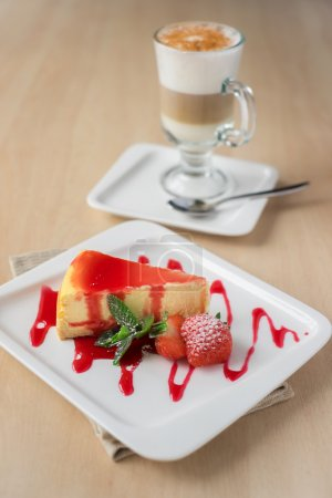 Cheesecake piece with strawberry sauce and berry, mint, icing sugar and a glass of coffee, selective focus