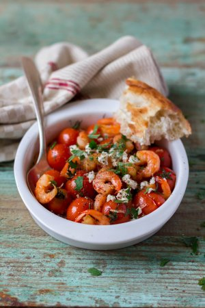 Roasted shrimps and tomatoes with feta cheese and garlic with homemade bread, selective focus