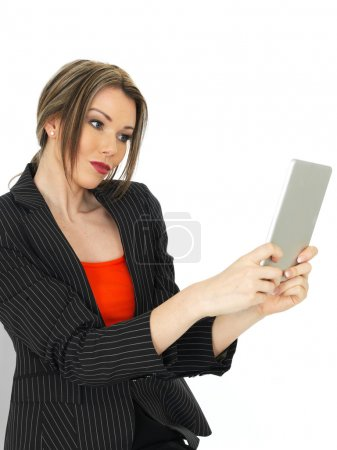 Photo for A DSLR royalty free image of an attractive young business woman, wearing a red top and dark jacket, using an electronic, wireless tablet, portable communications. Close up shots against a white background. Facial expressions and relaxed. - Royalty Free Image