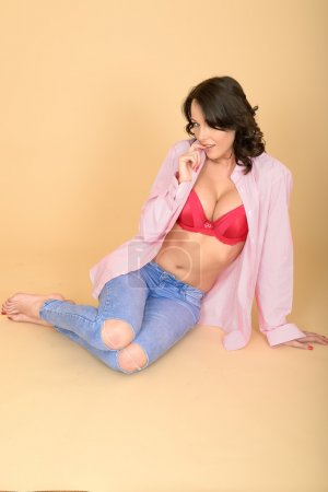 Attractive Young Woman Wearing Jeans and Shirt Revealling Her Re