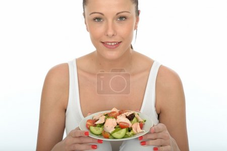 Photo for Healthy Happy Young Brunette Caucasian Woman, Wearing A White Summer Vest Top,  Eating Fresh Poached Salmon With A Mixed Garden Salad, Alone And Isolated On White - Royalty Free Image