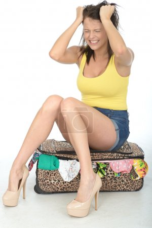 Angry Frustrated Young Sexy Young Woman Sitting on a Packed Suitcase