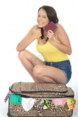 Happy Please Young Woman Kneeling on a Packed Suitcase Holding a Passport Travel Document