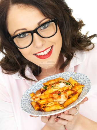 Photo for Pretty Young Woman in Her Twenties Wearing Black Framed Glasses Holding and Eating Penne Pasta - Royalty Free Image