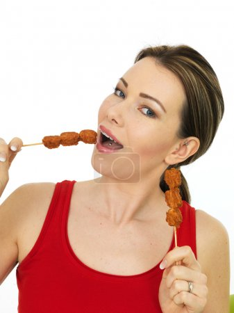 Attractive Young Woman Eating Chicken Satay Kebab Sticks